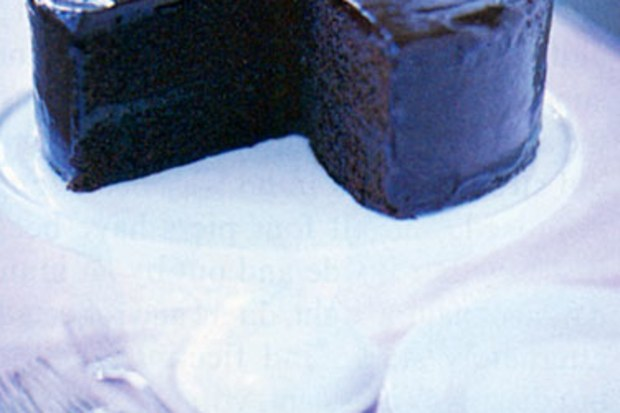 A low-quality photo of a chocolate cake on a cake stand, with the top of the cake cut off by poor cropping.